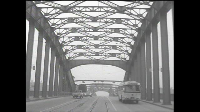 a bus passes cars on the kachidoki bridge in tokyo, japan. - 路面軌道点の映像素材/bロール