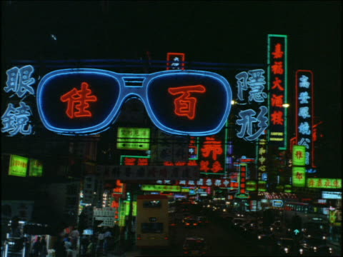 Bus point of view on city street past neon signs at night / Hong Kong