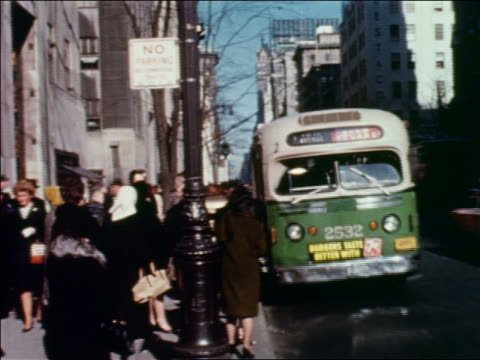 1960 bus pulling up to bus stop on city street with people waiting / people getting on bus / nyc - 1960 stock-videos und b-roll-filmmaterial