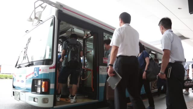 a bus sits parked at bus stop outside haneda airport in tokyo japan on wednesday sept 11 passengers board a shuttle bus a worker bows to customers as... - バス停留所点の映像素材/bロール