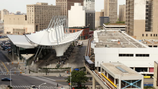bus station rosa parks transit center in detroit. people mover passing by. view from above. wide shot. michigan building in background. - spoonfilm stock-videos und b-roll-filmmaterial
