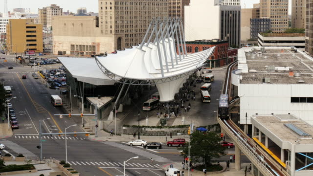 bus station rosa parks transit center in detroit. people mover passing by. view from above. medium wide shot. michigan building in background. - spoonfilm stock-videos und b-roll-filmmaterial