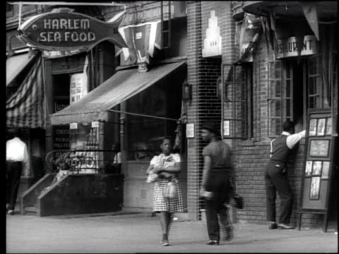 1939 b/w bus + store fronts on w. 130th with pedestrians, awnings / harlem seafood sign / woman selling clothes from cart on street, woman and child selling ices / new york city - harlem stock videos & royalty-free footage