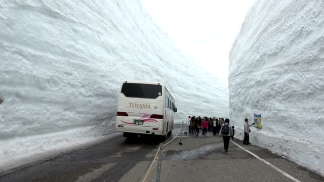 a bus travels through the famous snow canyon high in japan's tateyama mountains on 17th april 2018 - 深い雪点の映像素材/bロール