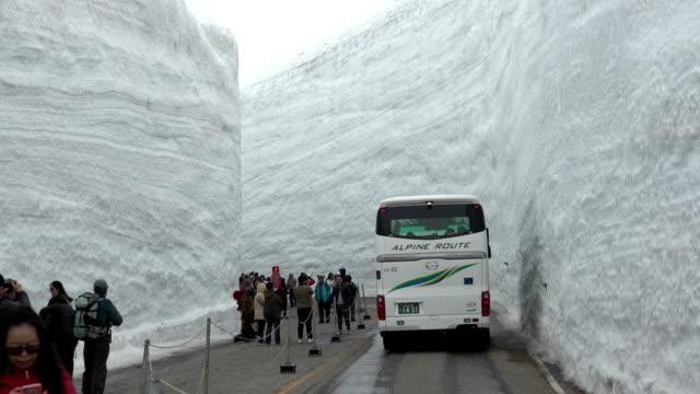 vidéos et rushes de a bus travels through the famous snow canyon high in japan's tateyama mountains on 17th april 2018 - hémisphère nord