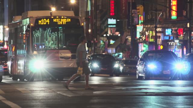 vídeos de stock e filmes b-roll de a bus waits at a stop light at night and drives off. - autocarro