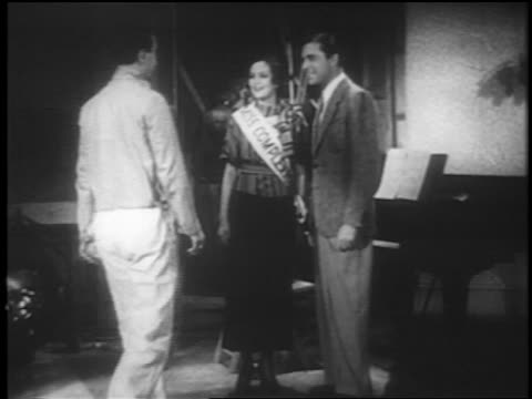 Busby Berkeley standing on set with couple talking / short