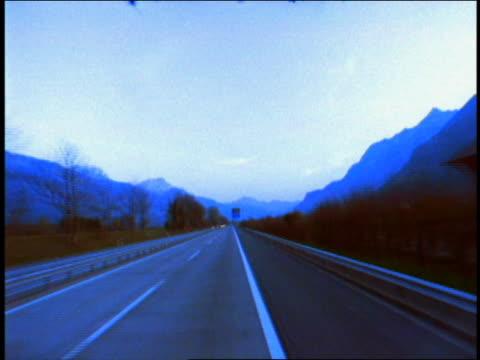 fast bus/car point of view on rural highway with mountains in background / switzerland - tonad bild bildbanksvideor och videomaterial från bakom kulisserna