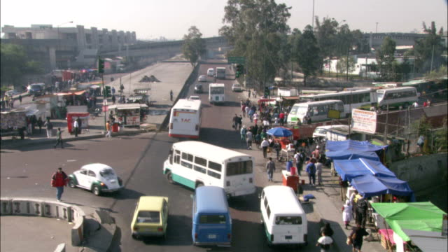 buses and cars move along a busy street in mexico. - mexico city stock-videos und b-roll-filmmaterial