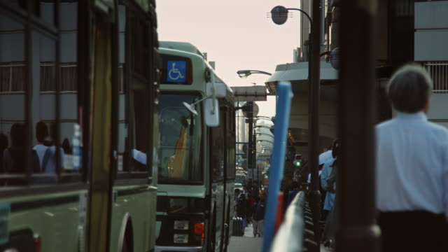 buses and people on shijo-dori in kyoto. - bushaltestelle stock-videos und b-roll-filmmaterial