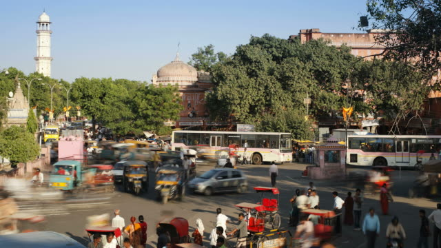 vídeos de stock, filmes e b-roll de buses, cars, and pedestrians all maneuver through the city of jaipur in india. - jinriquixá puxado por bicicleta