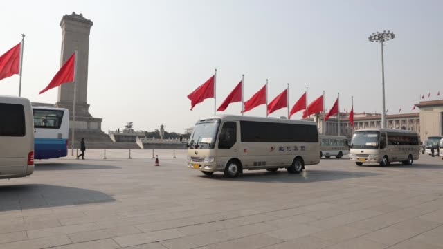 vídeos y material grabado en eventos de stock de buses drive past red flags near the great hall of the people in beijing china on saturday march 4 buses depart near the great hall of people... - puerta de la paz celestial de tiananmen