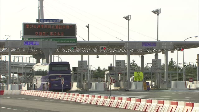 Buses pass through a ETC tollcollection gate of the access bridge to the airport / Shot on January 27 2009
