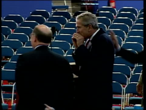 bush at mic, with hands up at mouth lms side bush at podium while wife, laura bush, paces about beside - laura bush stock videos & royalty-free footage