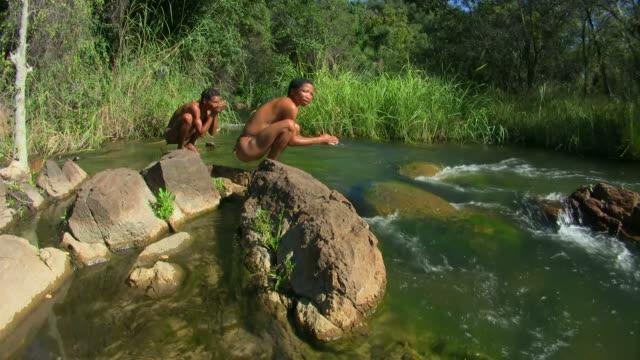 vídeos de stock, filmes e b-roll de bush pessoas em um rio - cultura indígena
