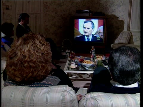 Defence cuts / economy ITN USA New Hampshire Manchester People sitting in room watching Bush speech on TV CMS Woman watching BV Man and woman ditto...