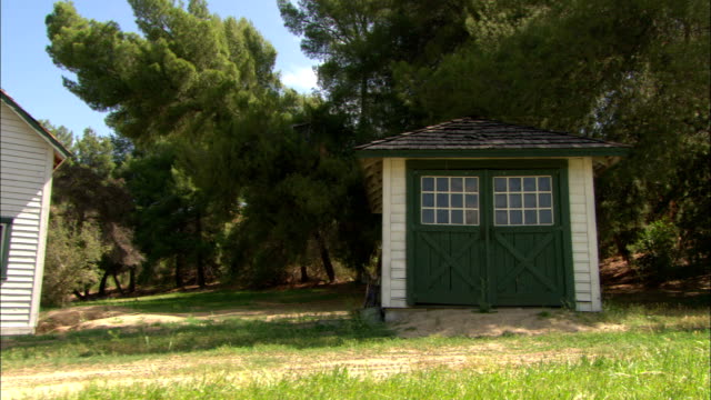 bushes and trees surround a shed with green doors next to a house and a pickup truck. - shed stock videos & royalty-free footage