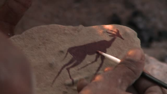vídeos y material grabado en eventos de stock de a bushman's hand paints the silhouette of an antelope on a thin slab of rock. available in hd. - pizarra roca metamórfica