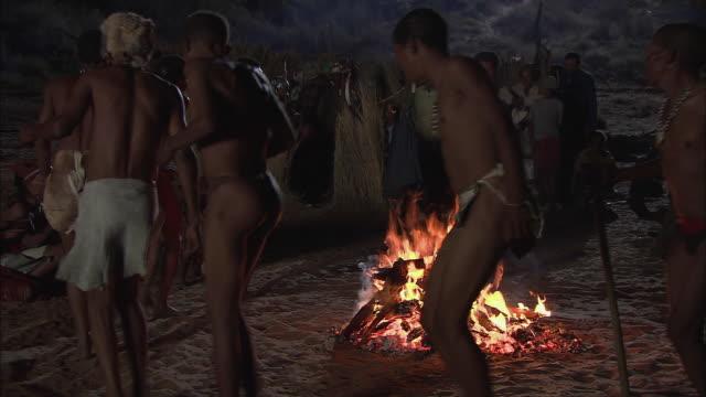 MS T/L Bushmen dancing around blazing bonfire / Kalahari Desert, North West, South Africa