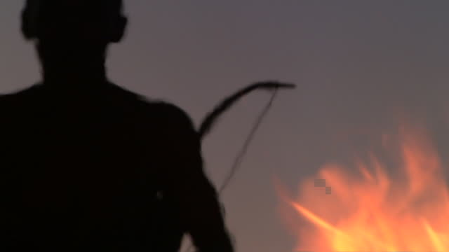 A Bushmen hunter carries a bow and arrow toward a blazing bonfire. Available in HD.