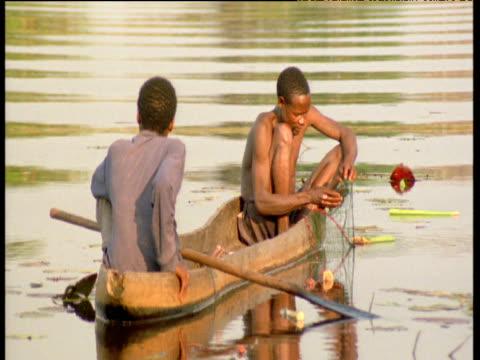 vídeos de stock, filmes e b-roll de bushmen remove fish from nets - indústria da pesca