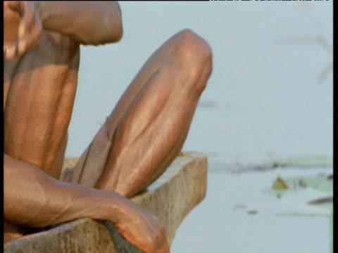 Bushmen remove fish from nets