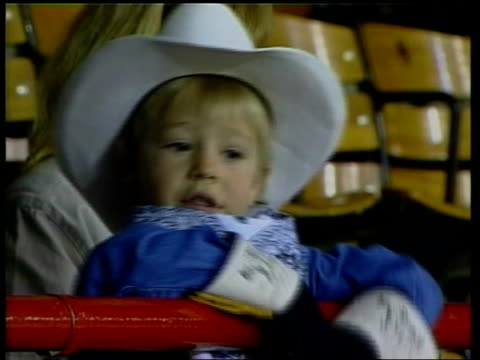 bush's backers c4n david colorado int tgv packed stadium for rodeo show ms children watching lms cowboy on horse holding us flag in centre of arena... - horse family video stock e b–roll