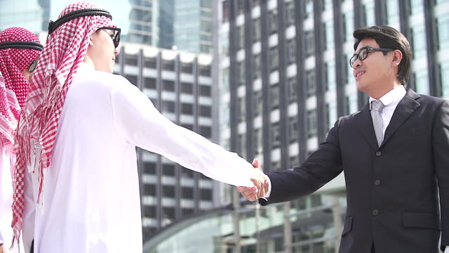 vídeos de stock e filmes b-roll de business and office concept - arab and asian businessman are shaking hand with cityscape as the background. - arábia saudita