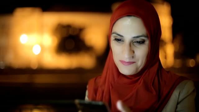 vídeos y material grabado en eventos de stock de mujer senior de negocios árabe usando teléfono móvil para chatear con amigos - de oriente medio