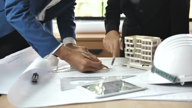 vídeos de stock e filmes b-roll de business architect people reviewing blueprints at desk - arquiteta