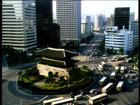 Business area of Seoul with high volume traffic circling traffic island which features traditional Korean pagoda.