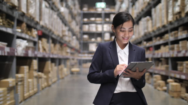 business asian women holding on digital tablet in her hand at warehouse. checking ordering in stock - leadership stock videos & royalty-free footage
