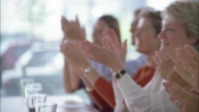 Business associates clap during a meeting.