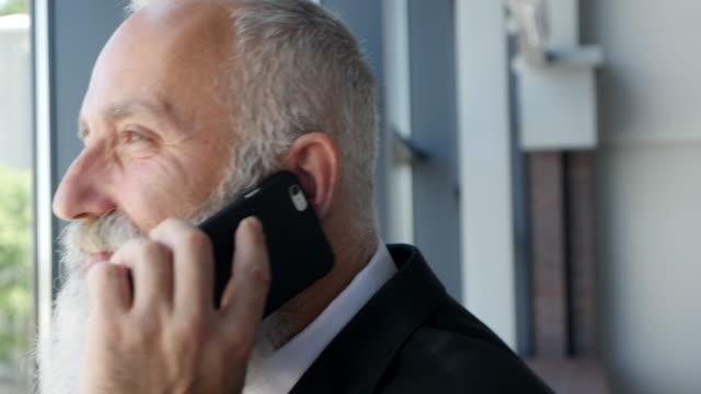 verksamhet. skäggiga affärsman pratar i telefon - 50 59 years bildbanksvideor och videomaterial från bakom kulisserna