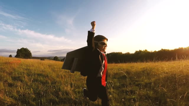 business boy runs through english field with jet pack - immaginazione video stock e b–roll