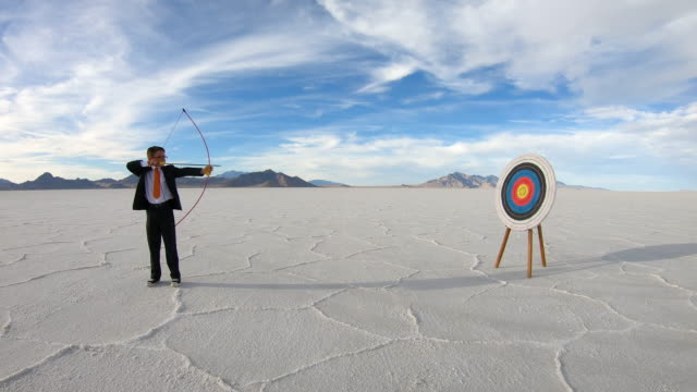 business boy shoots bow and arrow at target - risk stock videos & royalty-free footage