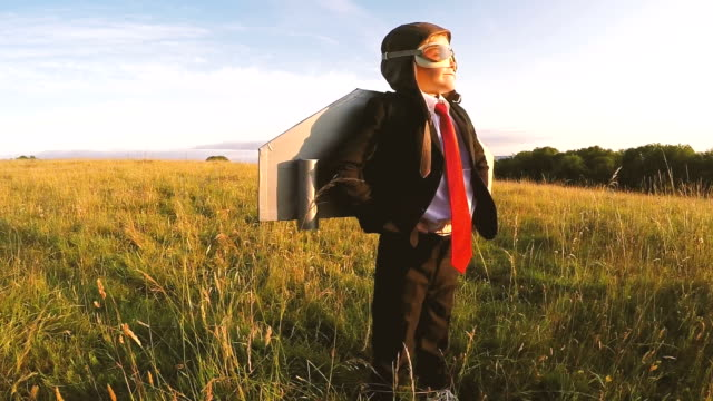 business boy stands confidently in english field with jet pack - immaginazione video stock e b–roll