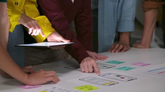 brainstorming e pianificazione aziendale di notte, primo piano del lavoro di squadra di sviluppatori e designer che lavorano a mano discutendo per la soluzione del design wireframe dell'interfaccia dell'app mobile nell'ufficio moderno. creativo per ux, tea - brainstorming video stock e b–roll