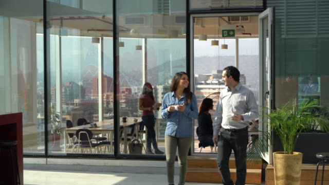 business colleagues at the office walking to the outdoor terrace of the office with a cup of coffee talking and smiling - fare una pausa video stock e b–roll