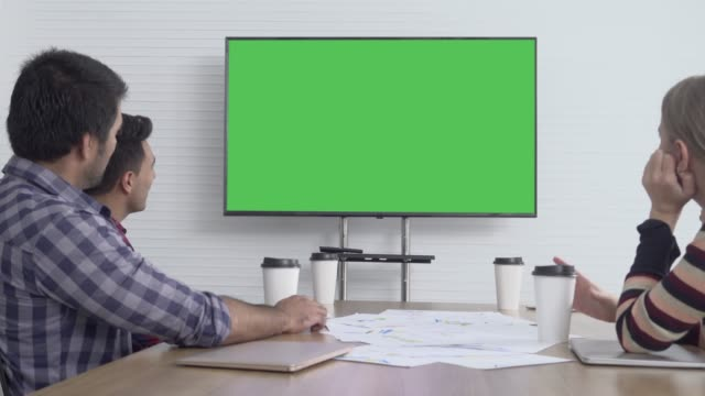 business colleagues attending a video call in conference room green screen - sala conferenze video stock e b–roll