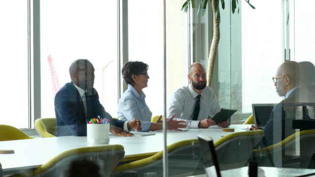 MS Business colleagues discussing project during team meeting in office conference room