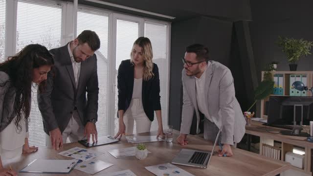 colleghi di business che discutono di soluzioni per un progetto a cui stanno collaborando - abbigliamento da lavoro formale video stock e b–roll