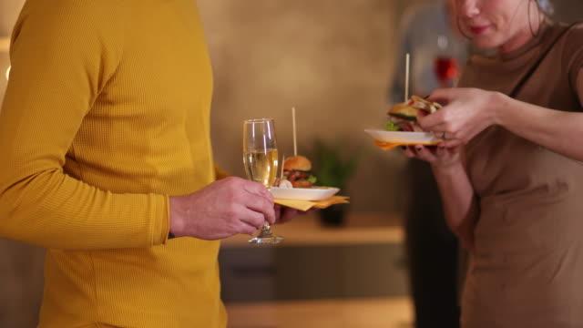 vidéos et rushes de collègues d'affaires mangeant des hamburgers pendant l'événement de réseautage - happy hour