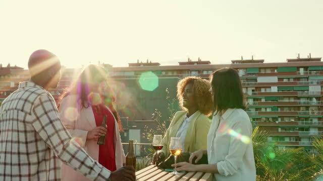 vídeos de stock e filmes b-roll de business colleagues enjoying drinks on rooftop at sunset - 20 29 anos