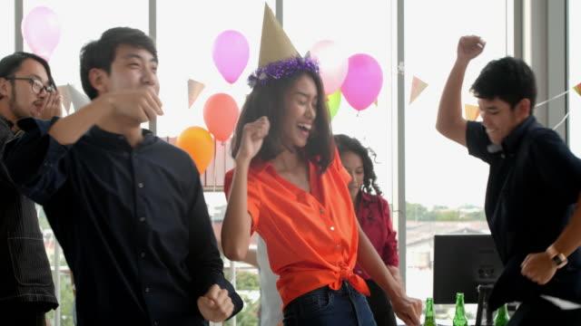 vídeos de stock, filmes e b-roll de festa no escritório de colegas de trabalho. equipe de negócios casuais comemorando com chifres de champanhe e festas no escritório - trabalhadora de colarinho branco