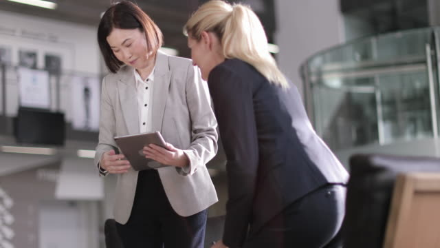 business colleagues in a meeting looking at a digital tablet - business点の映像素材/bロール