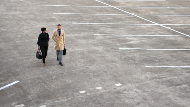 ms td business colleagues in discussion while walking through parking lot - parken stock-videos und b-roll-filmmaterial