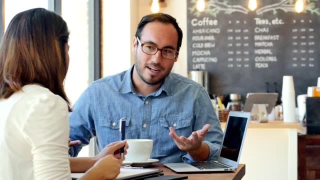 Business colleagues meet in a cafe to discuss their project before work