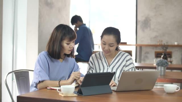 ビジネス部門の同僚が仕事の前に彼らのプロジェクトを議論するカフェで会う - カジュアルウェア点の映像素材/bロール