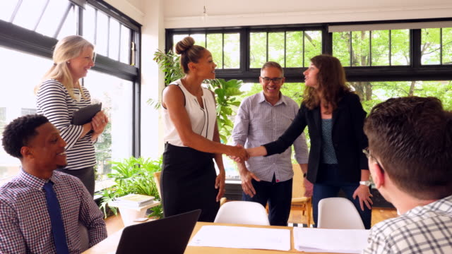 MS Business colleagues shaking hands after project meeting in start up office